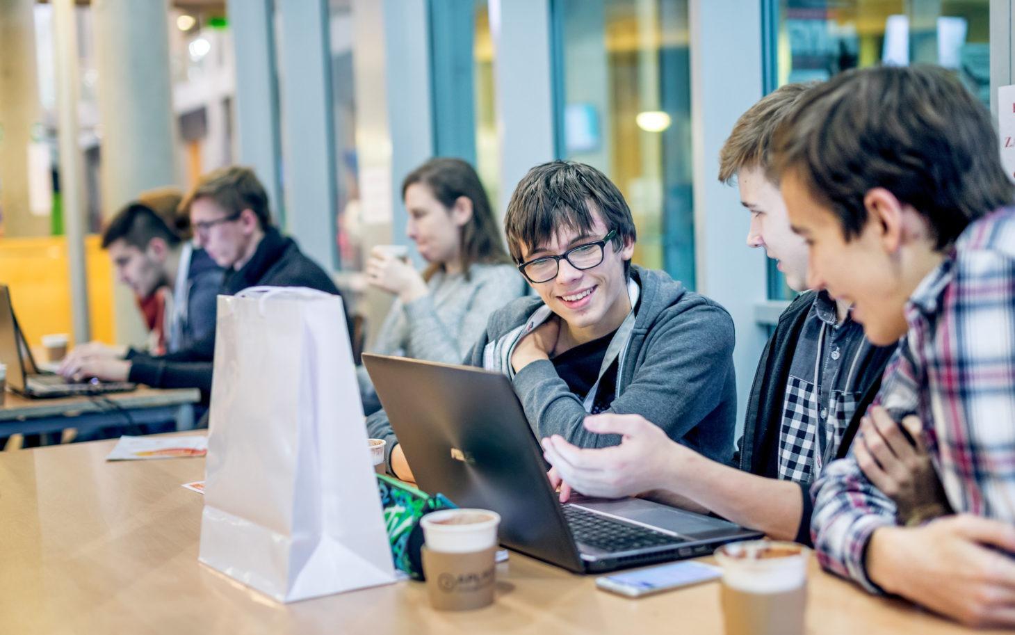 Na zdjęciu widać grupę uczniów, którzy omawiają to, co widzą na monitorze laptopa
