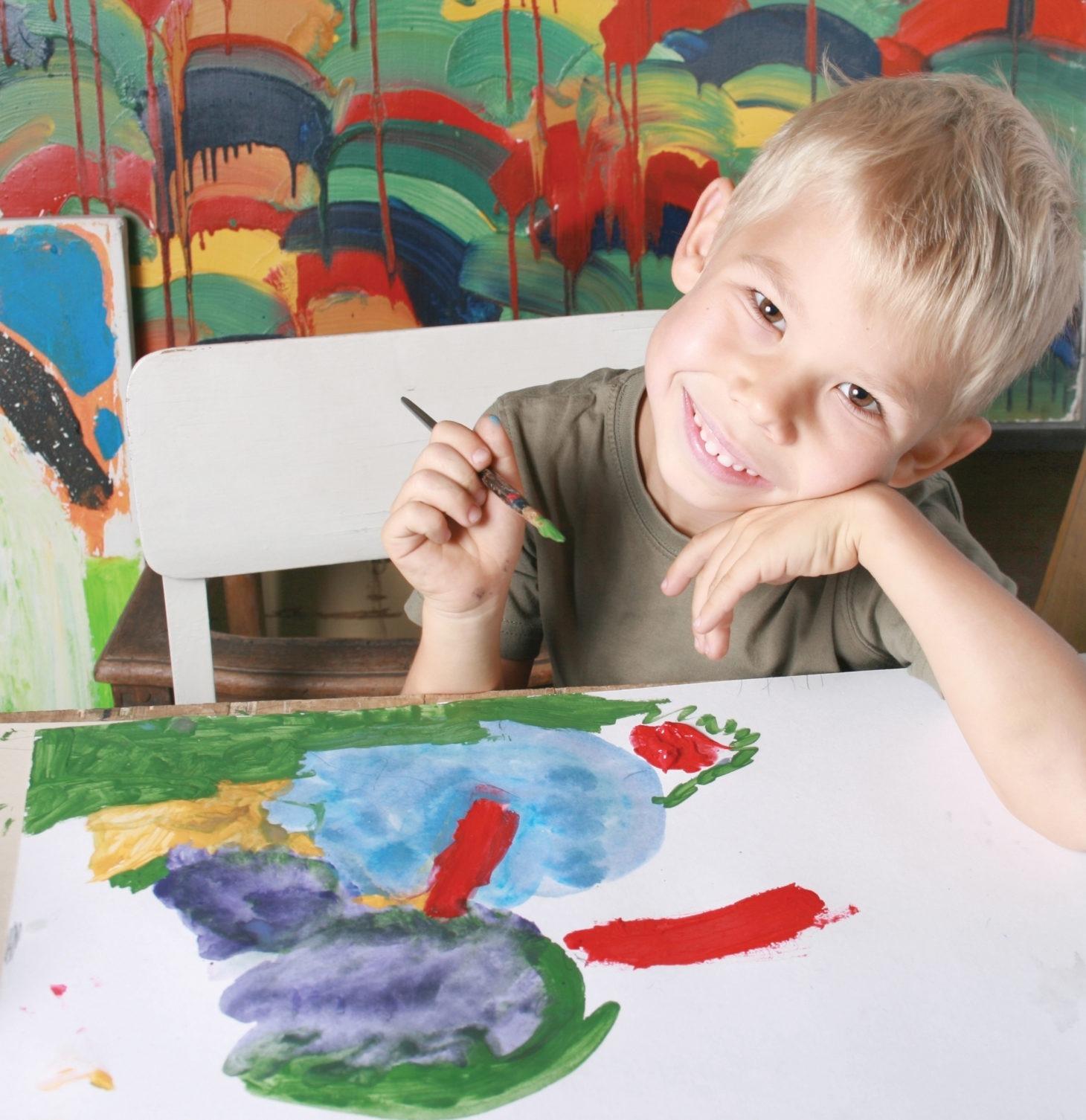Na zdjęciu widać uśmiechniętego chłopca, który maluje na kartce farbami