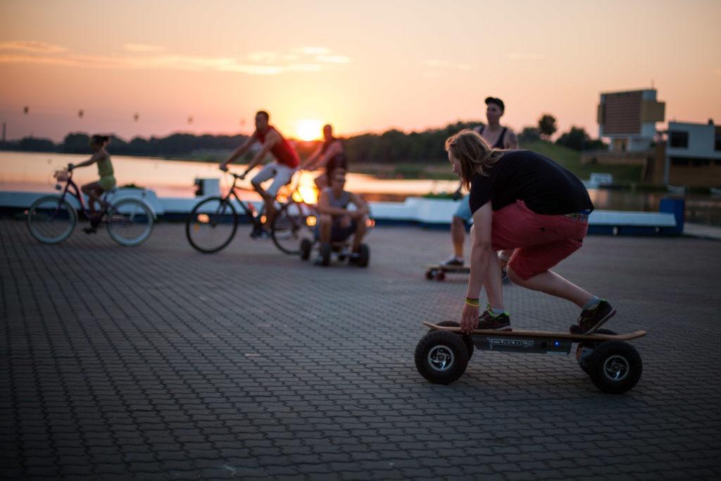 na zdjęciu widać młodzież jeżdżącą na deskorolkach i rowerach nad Maltą