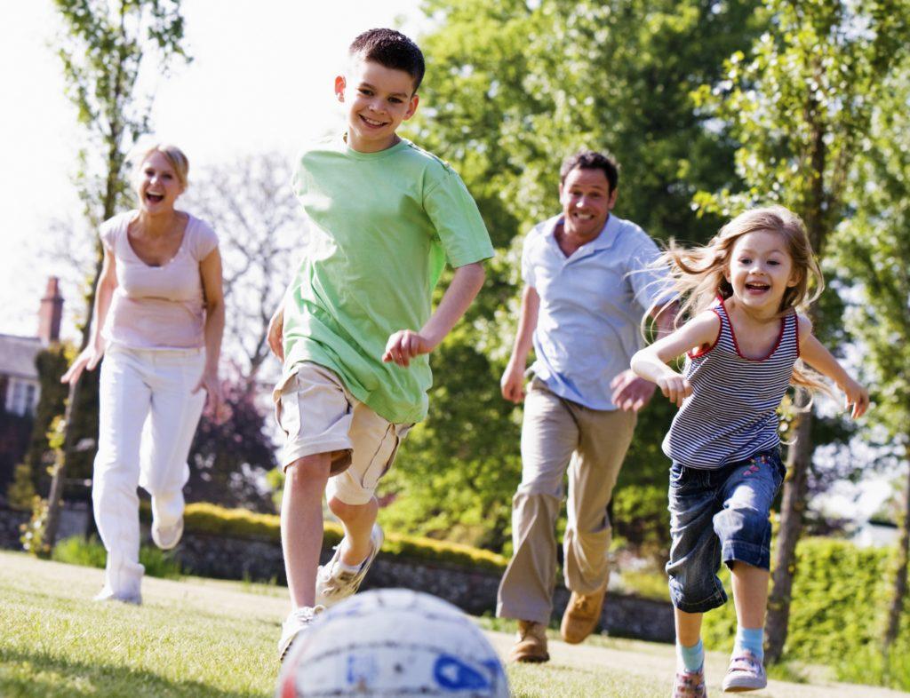 na zdjęciu widać uśmiechniętą rodzinę grającą w piłkę nożną