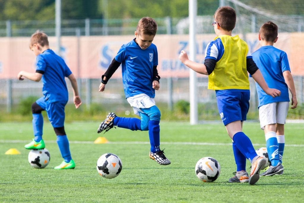 na zdjęciu widać chłopców grających w piłkę nożną na boisku
